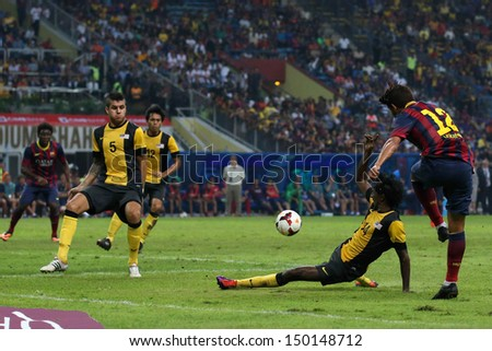 KUALA LUMPUR - AUGUST 10: Malaysia's Jayaseelan (14) blocks a shot by Barcelona's Jonathan Santos (12) in a friendly match at the Shah Alam Stadium on Aug 10, 2013 in Malaysia. Barcelona wins 3-1. - stock photo