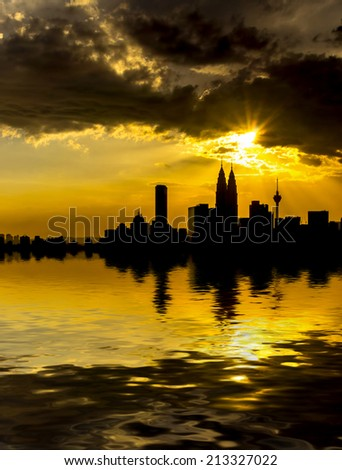 Kuala Lumpur City Center in silhouette during sunset surrounding with water flood. digital compositing with colour tone, water reflection and ripple effects. - stock photo