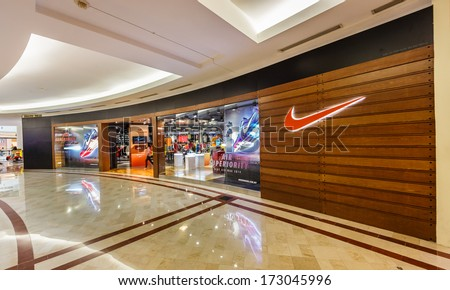 KUALA LUMPUR - DEC 23: Nike shop at KLCC on Dec 23,13 in KL. It is an American company, engaged in the design, development, manufacturing and marketing of footwear, apparel, equipment and services. - stock photo