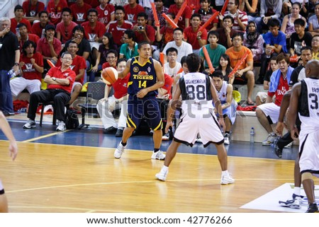 KUALA LUMPUR - DECEMBER 13: KL Dragons defends an attack by Thailand Tigers' Axel Doruelo in the ASEAN Basketball League match. December 13, 2009 in Kuala Lumpur. - stock photo