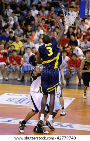 KUALA LUMPUR - DECEMBER 13: KL Dragons defends an attack by Thailand Tigers' Chaz Briggs (R) who scores with a lay-up in the ASEAN Basketball League match December 13, 2009 in Kuala Lumpur. - stock photo