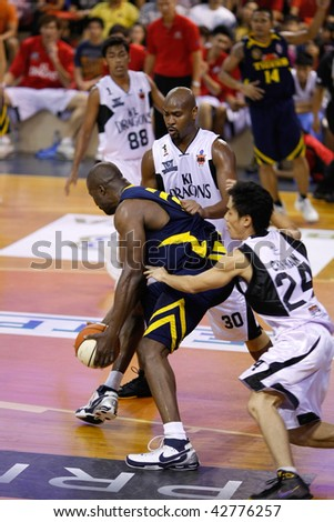 KUALA LUMPUR - DECEMBER 13: KL Dragons defends an attack by Thailand Tigers' Ikenna Nwankwo in the ASEAN Basketball League match. December 13, 2009 in Kuala Lumpur. - stock photo