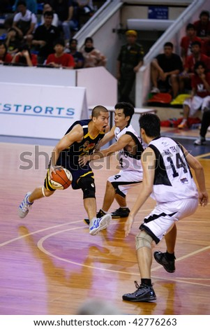KUALA LUMPUR - DECEMBER 13: KL Dragons defends an attack by Thailand Tigers' Ratdech Kruatiwa in the ASEAN Basketball League match. December 13, 2009 in Kuala Lumpur. - stock photo