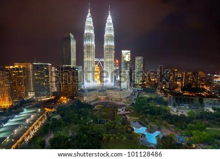 KUALA LUMPUR-JAN-23-2012: View of The Petronas Twin Towers at night on January 23, 2012 in Kuala Lumpur, Malaysia. Petronas are the tallest twin buildings in the world (451.9 m) - stock photo