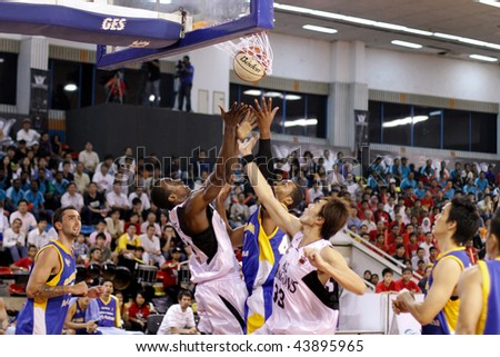 KUALA LUMPUR - JANUARY 05: KL Dragons' and Satria Muda BritAma players jump for the ball at the ASEAN Basketball League match January 05, 2010 in Kuala Lumpur. - stock photo