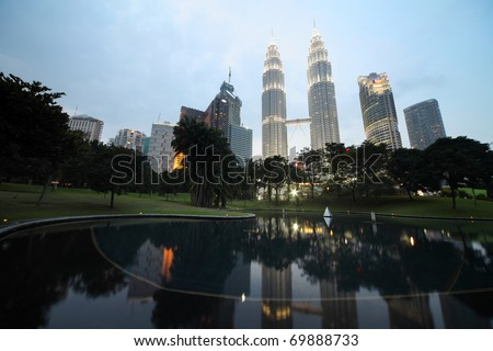 KUALA LUMPUR - JANUARY 22: Petronas Twin Towers - tallest twin buildings in the world at the evening light with reflection in a pond January 22, Kuala Lumpur, Malaysia - stock photo