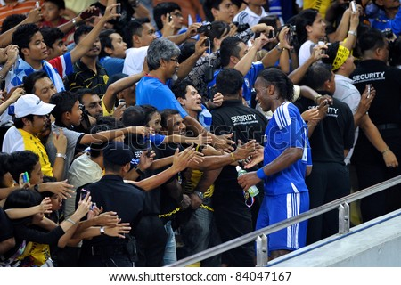 KUALA LUMPUR, July 21 : Chelsea's Didier Drogba shaking hands with fans during a preseason match agains Malaysia on July 21, 2011 in Kuala Lumpur, Malaysia. Chelsea won 1-0 - stock photo