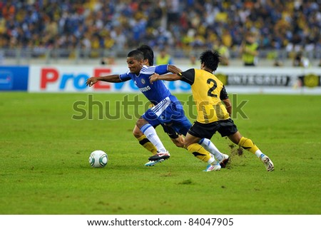 KUALA LUMPUR, July 21 : Chelsea's Florent Malouda (blue) and Malaysian Daudsu Jamaluddin (2) in action during a preseason match agains Malaysia on July 21, 2011 in Kuala Lumpur, Malaysia. - stock photo