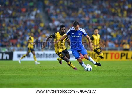 KUALA LUMPUR, July 21 : Chelsea's Paulo Ferreira (blue) and Malaysian Gary Stevan (12) in action during a preseason match agains Malaysia on July 21, 2011 in Kuala Lumpur, Malaysia. Chelsea won 1-0 - stock photo
