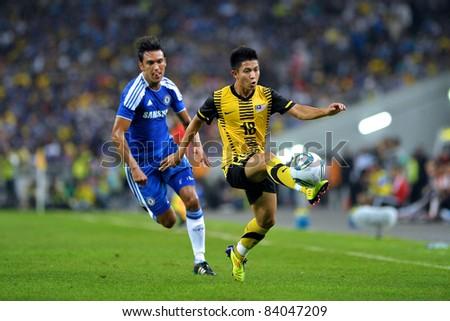 KUALA LUMPUR, July 21 : Chelsea's Paulo Ferreira (blue) and Malaysian Zaharul Nizam (18) in action during a preseason match agains Malaysia on July 21, 2011 in Kuala Lumpur, Malaysia. Chelsea won 1-0 - stock photo