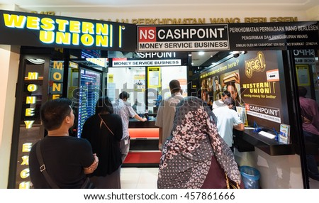 KUALA LUMPUR - JUNE 15, 2016: People send and exchange money in the Suria KLCC shopping mall. The mall is located in the Kuala Lumpur City Centre district near the famous Petronas Towers.