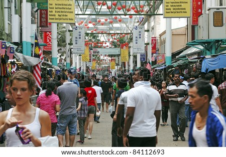 KUALA LUMPUR, MALAYSIA - AUGUST 30: Shoppers in the crowded street bazaar on August 30, 2011 in Chinatown, Kuala Lumpur, Malaysia. The district is earmarked for demolition by 2012 for a new train line - stock photo