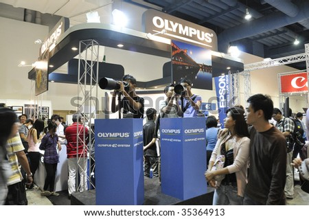 KUALA LUMPUR, MALAYSIA - AUGUST 15: Visitors in Olympus booth testing Olympus's camera and lens at Kuala Lumpur Photography Festival August 15, 2009 in Mid Valley Exhibition Center, Kuala Lumpur. - stock photo