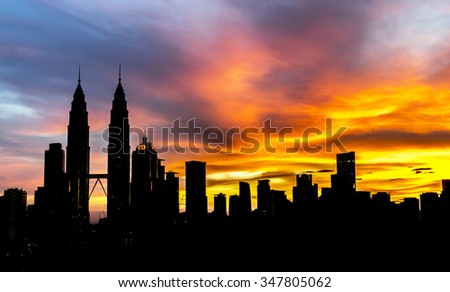 KUALA LUMPUR, MALAYSIA - DEC 6, 2015: The silhouette of KLCC Twin Towers with orange sunrise background with natural lighting.