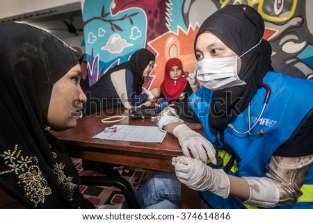 KUALA LUMPUR, MALAYSIA -1 DECEMBER 2015 :  Volunteering doctor from NGO giving free medical treatment to the people in need living in slum area.
