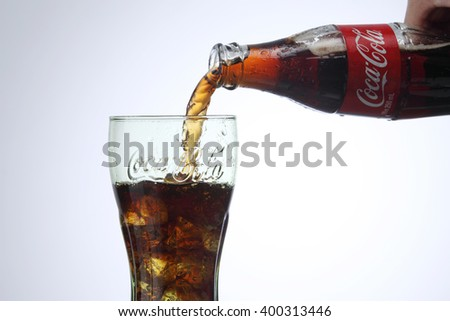 KUALA LUMPUR, MALAYSIA - Feb 17, 2016 pouring coca cola to a glass with ice cube - stock photo