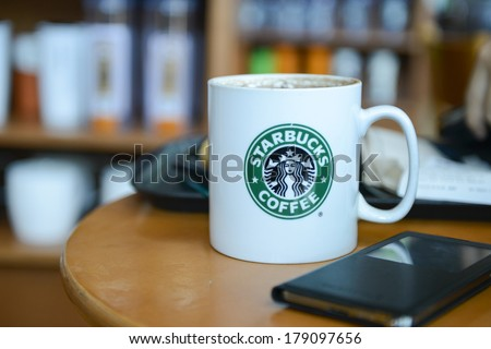 KUALA LUMPUR,MALAYSIA-FEBRUARY 28, 2014:Picture of cocoa cappuccino in a hot steamy mug and Samsung Galaxy Note 3 in Kuala Lumpur. Starbucks Malaysia franchise is owned by Berjaya Group Berhad company - stock photo