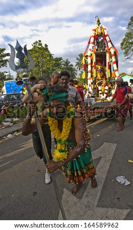 Kuala Lumpur, Malaysia, January 27 2013: A Hindu devotee pulls a chariot during Thaipusam festival to fulfill their vows and offer thanks to the deities.