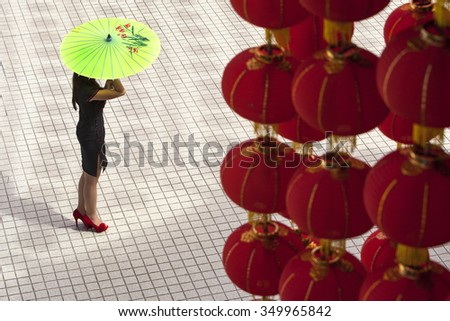 Kuala Lumpur, Malaysia, January 17, 2012:  A Malaysian lady walks under rows of lanterns at a temple square for the coming Chinese Lunar New Year celebration, the Year of the Dragon on the 23 January. - stock photo