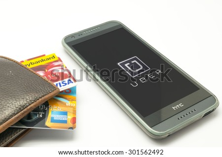 KUALA LUMPUR, MALAYSIA - JULY 31TH 2015. Visa credit card and Uber mobile apps. Uber allow consumers with smartphones to submit a trip request then routed to Uber drivers who use their own cars. - stock photo