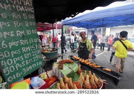KUALA LUMPUR, MALAYSIA : JUNE 19, 2015 - A stall hawker preparing food at his stall in a ramadhan bazaar. - stock photo