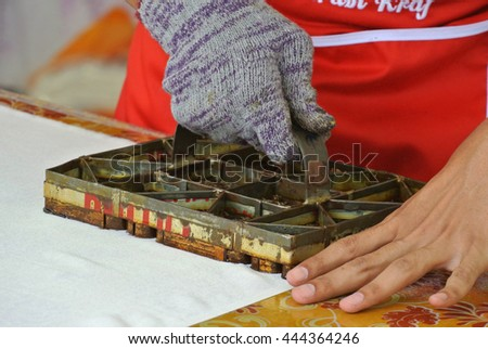 KUALA LUMPUR, MALAYSIA -JUNE 25, 2016: An artist press get batik pattern using the mold or pattern block of batik tekap or stamp batik.  The block was made from metal & copper.