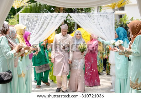 Kuala Lumpur, Malaysia  March 22, 2014. Just married Malay couple walking and holding hands is being congratulating by their guests. - stock photo