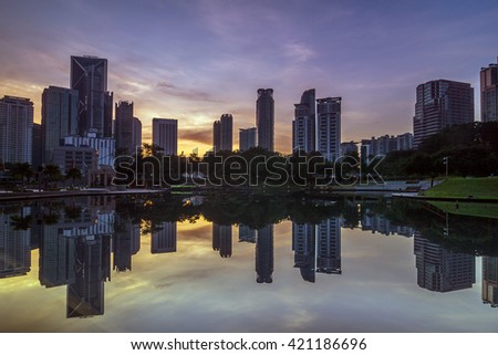 Kuala Lumpur Malaysia 7 May 2016: city at a lake with beautiful sky reflection during sunrise (soft focus, shallow DOF, slight motion blur)