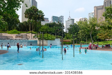 KUALA LUMPUR, MALAYSIA - 02 NOV 2014: Children at the pool in Kuala Lumpur urban area KL Central Park with buildings in the background, having fun outdoors. - stock photo