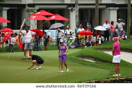 KUALA LUMPUR, MALAYSIA - OCTOBER 16: Aman Blumenherst (black) prepares for her putt on day 4 of the Sime Darby LPGA Malaysia 2011 golf tournament on Oct 16, 2011 in Kuala Lumpur, Malaysia. - stock photo