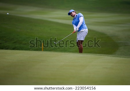 KUALA LUMPUR, MALAYSIA - OCTOBER 10, 2014: Ariya Jutanugarn of Thailand chips the ball to the 18th hole of the KL Golf & Country Club at the 2014 Sime Darby LPGA Malaysia golf tournament. - stock photo