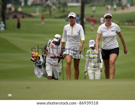 KUALA LUMPUR, MALAYSIA - OCTOBER 16: Azahara Munoz and Brittany Lang approaches the green of the KL Golf & Country Club at the Sime Darby LPGA Malaysia 2011 on Oct 16, 2011 in Kuala Lumpur, Malaysia. - stock photo