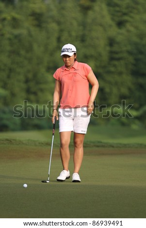 KUALA LUMPUR, MALAYSIA - OCTOBER 16: Candie Kung of Chinese Taipei prepares for her putt on day 4 of the Sime Darby LPGA Malaysia 2011 golf tournament on Oct 16, 2011 in Kuala Lumpur, Malaysia. - stock photo