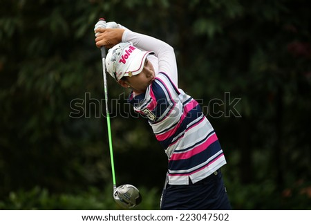 KUALA LUMPUR, MALAYSIA - OCTOBER 11, 2014: Chella Choi of South Korea tees off at the fourth hole of the KL Golf & Country Club during the 2014 Sime Darby LPGA Malaysia golf tournament. - stock photo