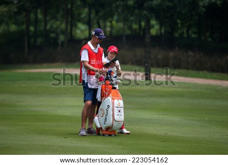 KUALA LUMPUR, MALAYSIA - OCTOBER 10, 2014: Eun-Hee Ji of South Korea discusses with her caddy on the fairway of the ninth hole of the KLGC Club at the 2014 Sime Darby LPGA Malaysia golf tournament. - stock photo