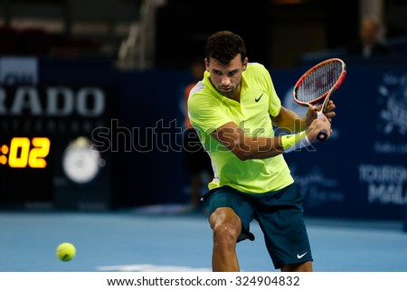 KUALA LUMPUR, MALAYSIA - OCTOBER 01, 2015:Grigor Dimitrov of Bulgaria attempts a backhand return in his match at the Malaysian Open 2015 Tennis tournament held at the Putra Stadium, Malaysia. - stock photo