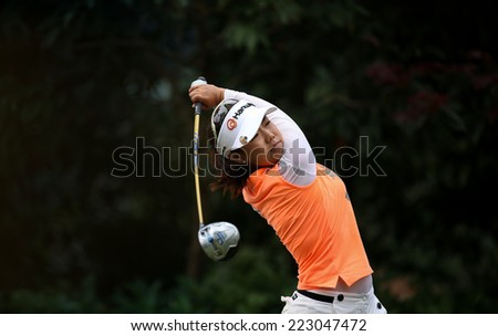 KUALA LUMPUR, MALAYSIA - OCTOBER 11, 2014: Jenny Shin of the USA tees off at the fourth hole of the KL Golf & Country Club during the 2014 Sime Darby LPGA Malaysia golf tournament. - stock photo