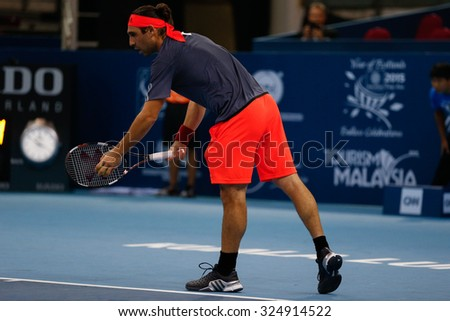 KUALA LUMPUR, MALAYSIA - OCTOBER 01, 2015: Marcos Baghdatis of Cyprus prepares to serve during his match at the Malaysian Open 2015 Tennis tournament held at the Putra Stadium, Malaysia. - stock photo