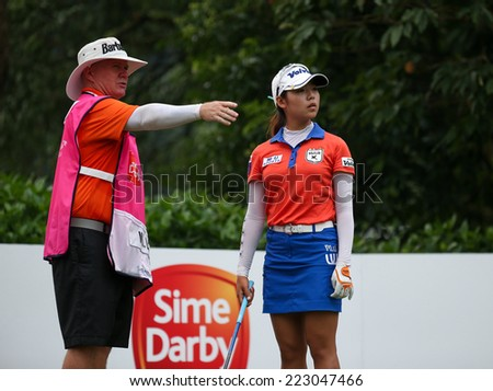 KUALA LUMPUR, MALAYSIA - OCTOBER 11, 2014: Mi Hyang Lee of South Korea listens to her caddy at the fourth hole of the KL Golf & Country Club during the 2014 Sime Darby LPGA Malaysia golf tournament. - stock photo