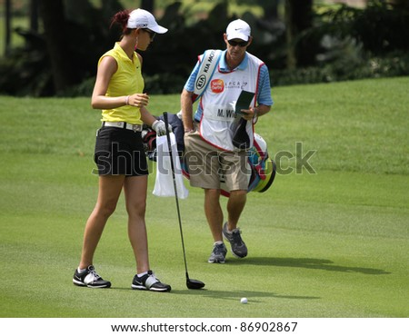 KUALA LUMPUR, MALAYSIA - OCTOBER 16: Michelle Wie of the USA discusses with caddie on the fairway of hole #9 during the Sime Darby LPGA 2011 golf tournament on Oct 16, 2011 in Kuala Lumpur, Malaysia. - stock photo