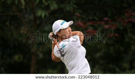 KUALA LUMPUR, MALAYSIA - OCTOBER 11, 2014: Mirim Lee of South Korea tees off at the fourth hole of the KL Golf & Country Club during the 2014 Sime Darby LPGA Malaysia golf tournament. - stock photo