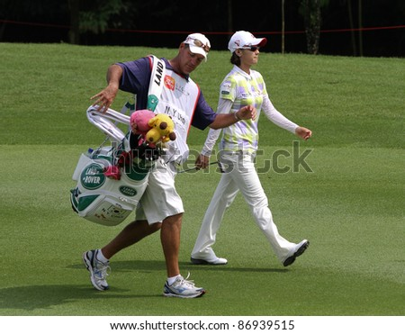 KUALA LUMPUR, MALAYSIA - OCTOBER 16: Na Yeon Choi of South Korea walks with her caddie on the fairway at the Sime Darby LPGA Malaysia 2011 golf tournament on Oct 16, 2011 in Kuala Lumpur, Malaysia. - stock photo