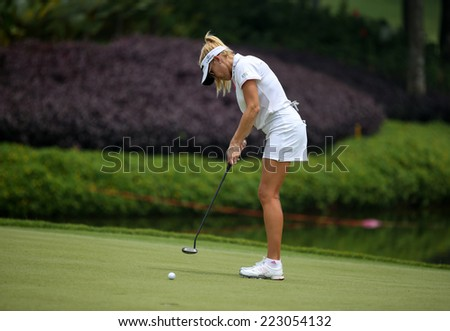 KUALA LUMPUR, MALAYSIA - OCTOBER 10, 2014: Natalie Gulbis of the USA putts the ball to the 18th hole of the KL Golf & Country Club at the 2014 Sime Darby LPGA Malaysia golf tournament. - stock photo