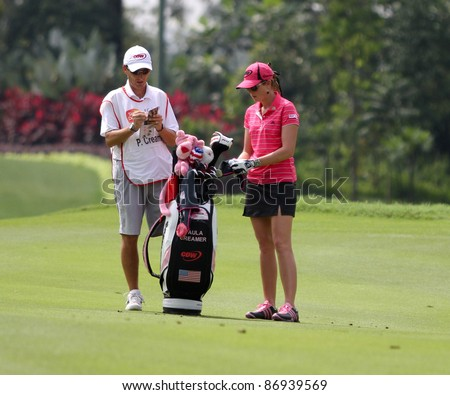 KUALA LUMPUR, MALAYSIA - OCTOBER 16: Paula Creamer of the USA discusses with her caddie on day 4 of the Sime Darby LPGA Malaysia 2011 golf tournament on Oct 16, 2011 in Kuala Lumpur, Malaysia. - stock photo