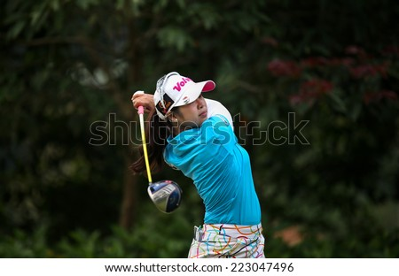 KUALA LUMPUR, MALAYSIA - OCTOBER 11, 2014: Pornanong Phatlum of Thailand tees off at the fourth hole of the KL Golf & Country Club during the 2014 Sime Darby LPGA Malaysia golf tournament. - stock photo