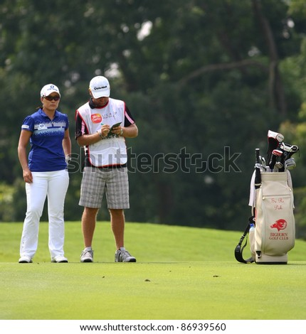 KUALA LUMPUR, MALAYSIA - OCTOBER 16: Se Ri Pak of South Korea discusses with caddie at hole #9 on day 4 of the Sime Darby LPGA Malaysia 2011 golf tournament on Oct 16, 2011 in Kuala Lumpur, Malaysia. - stock photo