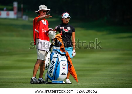KUALA LUMPUR, MALAYSIA - OCTOBER 09, 2015: South Korea's Mi Hyang Lee discusses with her caddy on the fairway of the KL Golf & Country Club at the 2015 Sime Darby LPGA Malaysia golf tournament. - stock photo