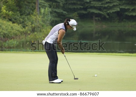 KUALA LUMPUR, MALAYSIA - OCTOBER 15: South Korean Se Ri Pak sinks her putt on the green on Day 3 of Sime Darby LPGA Golf October 15, 2011 in Kuala Lumpur, Malaysia. - stock photo