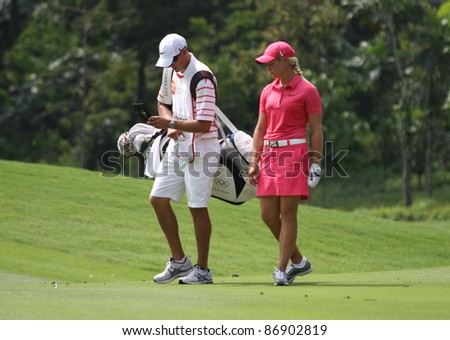 KUALA LUMPUR, MALAYSIA - OCTOBER 16: Suzann Pettersen of Norway discusses with her caddie during the Sime Darby LPGA Malaysia 2011 golf tournament on Oct 16, 2011 in Kuala Lumpur, Malaysia. - stock photo