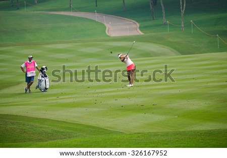 KUALA LUMPUR, MALAYSIA - OCTOBER 10, 2015: USA's Alison Lee plays on the fairway of the 18th hole of the Kuala Lumpur Golf & Country Club during the 2015 Sime Darby LPGA Malaysia golf tournament. - stock photo